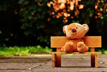 teddy bear sitting on bench in a park